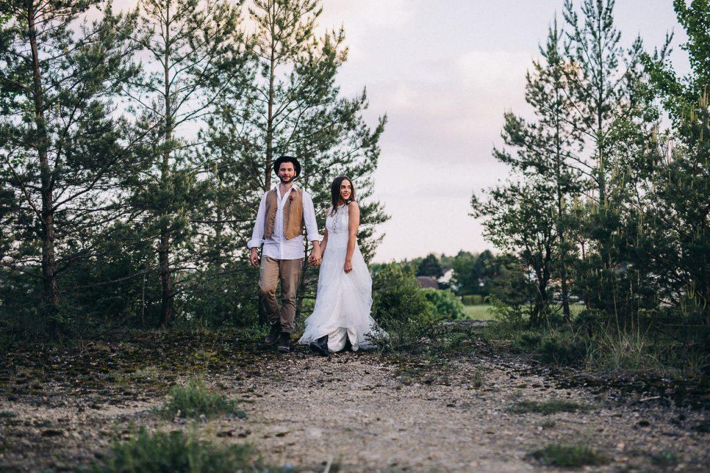 Boho Hochzeit Brautpaar läuft in der Natur