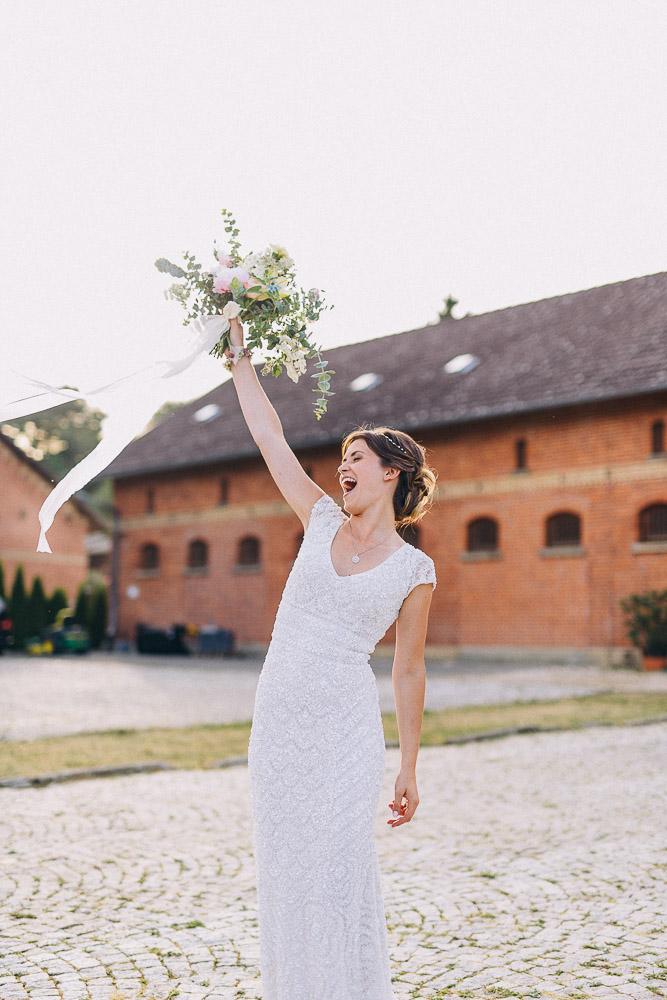 Braut streckt ihren Brautstrauß voller Freude hoch