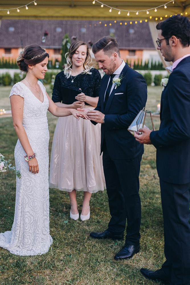 Bräutigam steckt Braut Ring an