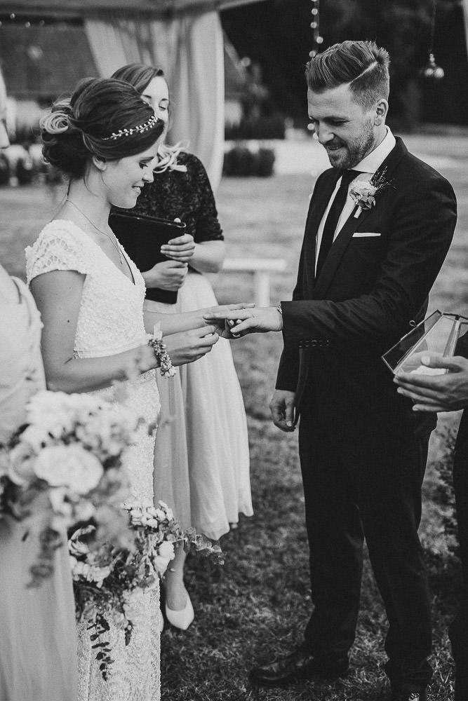 Braut steckt Bräutigam Ring an