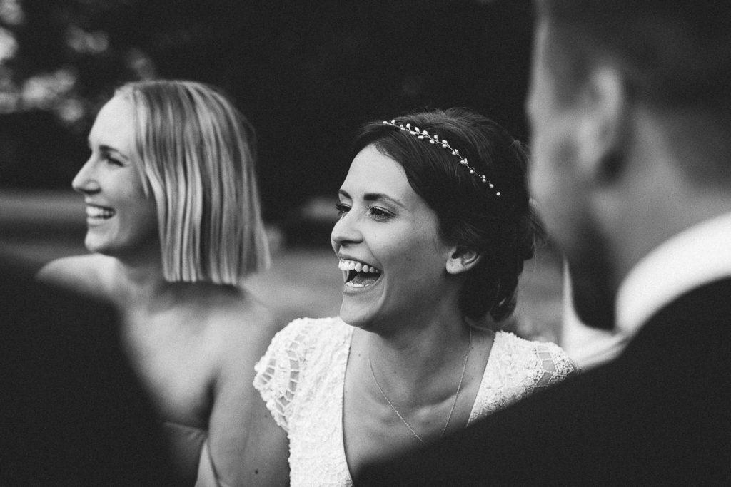 Braut lacht Gäste an bei freier Trauung